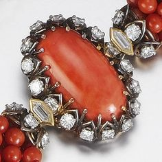 A coral and diamond necklace, by Cartier Designed as a torsade of eight rows of coral beads, to an oval cabochon coral clasp set with brilliant and hexagonal-cut diamonds, diamonds approximately 3.00 carats total, signed Cartier London and numbered.