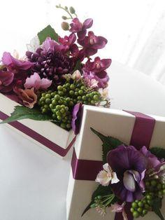 箱から溢れんばかりのお花でいっぱい。  日頃の感謝をお花と共に届けましょう。 ピオニー・4種混合あじさい・デンファレ  どの角度から見ても、BOXの中はお花でいっぱい。 フタ部分にもたっぷりアレンジ。 BOXから溢れ出るお花に息を飲んでしまうかも… BOXサイズ:13×13×10cm 仕上がり :15×15×16cm