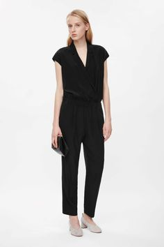 Crossing over at the front, this sleeveless jumpsuit is made from soft, lightweight silk. A loose fit, it comes in at the waist and has tapered legs, notched lapels and two slanted front pockets. It is secured with a hidden button fastening.
