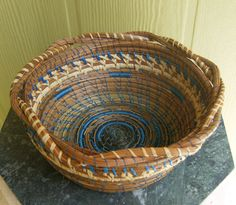 This basket is coiled with natural pine needles and dyed pine needles stitched together with blue sinew and raffia in a variety of stitches for design , ending with a rim of braided coils. The finished product has 2 coats of polycrylic sealer for stiffness and durability, which also makes it waterproof.. It is 7 inches in diameter and 3 inches tall.