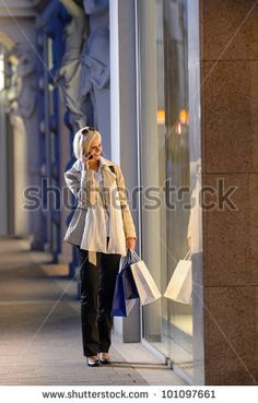 stock photo : Young woman shopping evening city looking into shop windows phone