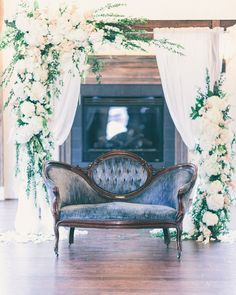 Vintage blue velvet sofa and gorgeous floral decor. Image by Rachel May Photography.