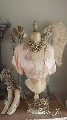Dress form with angel wing in background and bridal wax crow accents