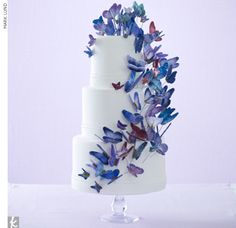 Three-tiered white, fondant wedding cake covered with a cascade of sugar-molded and hand-painted purple butterflies.