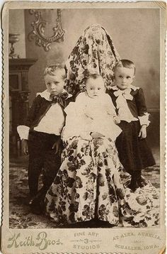 A 'hidden mother' photograph.  In the Victorian Era, women holding infants were often covered because the photograph is meant to be cropped and framed to show only the infant.  The original photograph is creepy.  These photos are usually taken with a black fabric, not a print.  Passport photos of infants are still taken this way in some countries.
