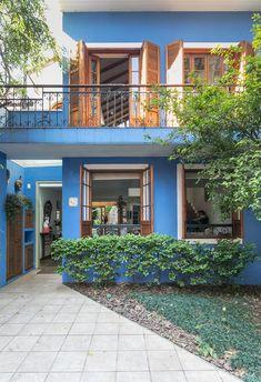 Casa de dois andares tem fachada com parede azul, janelas de madeira e sacada com grade de ferro.
