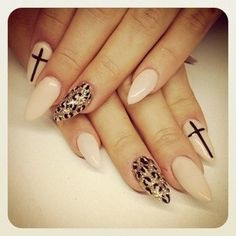 Nude stiletto nails with cross and leopard accent.