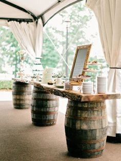 Rustic cake and dessert table made with old whiskey barrels. Cottage chic wedding decor.
