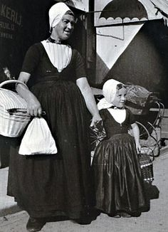 Walcheren - Vrouw en meisje in Walcherse dracht op een marktdag, Middelburg, omstreeks 1910 (ZA/HTAM)   Kenmerkend voor de Walcherse vrouwendracht is de kleine hulmuts die als bovenmuts gangbaar blijft. Ook de traditionele combinatie van jak, beuk, rokken en schort voor de vrouwen blijft al die tijd behouden. De doek verdwijnt hier in de loop van de tijd steeds verder in het jak.
