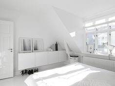 On the upper floors, bright white walls and plenty of natural light make the bedrooms and living rooms feel large and spacious. In the master bedroom, built-in cabinetry hides clutter. The art photography against the wall is by Anders Hviid, the bed is Hästens, the laundry basket is Vipp, and the lamp is Fontana Arte.