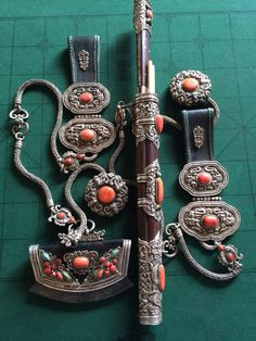 A knife set, equipped with a pair of chopsticks, a tinder pouch, a pair of belt pendants and two toggles. 19th century, Mongolian. Silver, coral, turquoise, steel, ivory, wood and leather.