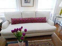 This sofa was a redo from an old, out-dated couch.  They got rid of the seat cushions, recovered, and accented with beautiful, long magenta pillow and flowers.  So lovely.