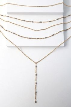 "Accessorize in style with the Roma Gold layered Necklace! Layers of gold chains cascade delicately down to a center drop chain. Grey beads add detail throughout. Shortest layer measures 15"" long with a 3"" extender chain."