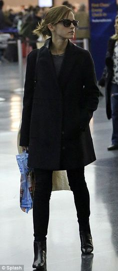 Dark: Emma opted for a black long coat, jeans and boots to travel in on Sunday