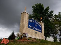 Flowers lie on the sign to the Sikh temple of Wisconsin where members were allowed to re-enter for the first time in Oak Creek, Wis., Thursday, Aug 9, 2012. (AP Photo/Jeffrey Phelps)