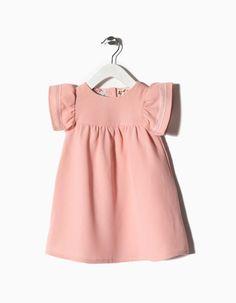 Vestido texturado em algodão e viscose. Mangas borboleta com detalhe. Botões madrepérola atrás para vestir facilmente.