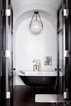 Arched subway tile nook with clawfoot tub and modern pendant--image via greige design
