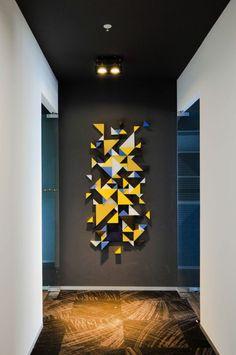 une idée pour un pan de mur aux motifs graphiques en formes de triangles en jaune et bleu roi, sol effet usé, murs blancs, plafond noir