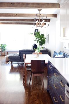 SPANISH REMODEL: KITCHEN + FAMILY ROOM | E. INTERIORS  Spanish modern charm at it's finest. This remodel included a new kitchen, and added breakfast nook, a new fireplace and these amazing reclaimed wood beams to tie everything together.