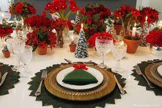 mesa de natal verde e vermelha com flores vermelhas e dobradura de guardanapo em forma de árvore de natal