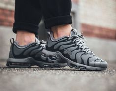 The Nike Air Max Plus TN Ultra in black/grey is showcased in a lifestyle perspective. Find it at select Nike stores overseas first.