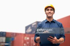 Stock Photo : Smiling young engineer in protective work wear in a shipping yard examining cargo