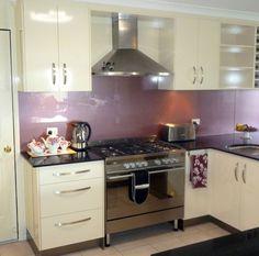 Purple glass splash back complements cream kitchen cabinets