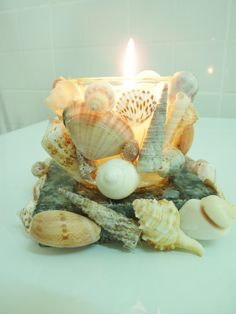 My own creation. Glass votive candle holder, granite scrap base. Hot glue shells from the Sea of Oman!