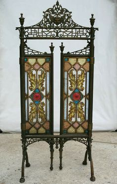 A good antique bronze and stained glass fireplace screen having a winged figure crest over hinged stained glass doors circa 1890. Supported on down swept legs with paw feet.