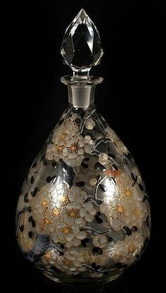 DELVAUX 1920'S ART GLASS PERFUME BOTTLE. (Circa 1920's) Delvaux French art glass perfume bottle, clear blown glass bottle with ground and polished pontil bottom, decorated with black, white and gilt blossoming branch overall decoration