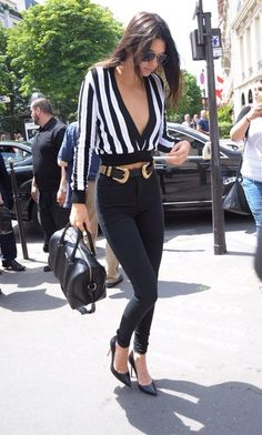 $22 - $640 Kendall Jenner takes black and white pieces to streetstyle glam in a pair of black pants and pumps, deep v neck striped blouse, black duffle bag and statement gold inspired belt.
