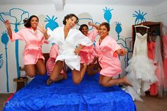 Bridesmaids and bride jumping on the bed before a destination wedding in Tulum at the Akiin Beach Club. Mexico wedding photographers Del Sol Photography.