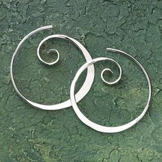 "Koru Spiral Earrings Named by the Maori for the spiral-shaped fern of New Zealand, the koru reaches toward the light—strives for perfection—represents new beginnings. These koru earrings are hammer-textured sterling silver. Handcrafted. 1"" diam. (approx.).	  ****"