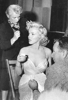 Marilyn Monroe getting her hair touched up by her hairdresser.