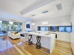 hardwood floor, waterfall breakfast bar, pendant lighting, bulkhead defining the kitchen space in an open plan floor plan. Clean bright, functional