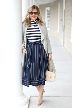 Krystin Lee from Suburban Faux Pas looks fabulous in a double stripe look. She styles a blue and white horizontal striped turtleneck with our navy and white pinstripe midi skirt. She keeps the rest of her look neutral with a light gray overcoat, nude pumps and a blush shoulder bag | Banana Republic