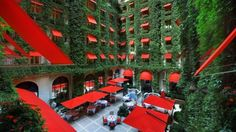 This striking color combination of cherry red sun awnings, parasols and dining seats against a dense covering of exquisitely lush ivy is the...