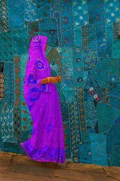 Woman walking past a tapestry - Jodphur, Rajasthan, India