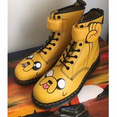 Dr Martens x Adventure Time Jake Boot ✨Women's US size 11 For every day adventures, in the Land of Ooo and beyond, this is the boot. A tribute to Adventure Time's magical, shape-shifting Jake the Dog, it's crafted in yellow Smooth leather, with Jake's jowly face on the toe and a padded, lace-through over-strap shaped like his hand.     Please only submit offers through the offer button. Dr. Martens Shoes Combat & Moto Boots
