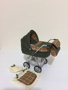 PLEASE ALLOW UP TO TWO WEEKS FOR DELIVERY AS THIS ITEM IS MADE TO ORDER Green needlecord fabric ,miniature pram/stroller/buggy. With contrasting check lining, complete with crotchet cover and pillow to match Wheels turn freely and the bag is removable All my miniatures are hand crafted by me to a high standard. These items are collectible miniatures, not toys so are not suitable for children under 14 This item is available to ship immediately