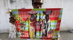 Artist Lia Annickson shows one of his paintings in a street in Abidjan, Ivory Coast, 29 March