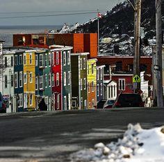 """IlPost - St. John's, Canada - Si trova sull'isola di Terranova, ed è una cittadina con delle strade piccole e tortuose affiancate da una schiera di case colorate. C'è una ragione per cui il centro della città viene chiamato Jellybean Row (più o meno """"Fila delle caramelle gelatinose""""): in passato i capitani delle navi che arrivavano sull'isola di Terranova avrebbero dipinto le proprie case con dei colori molto accesi per renderle più visibili dal mare. Per il suo aspetto, St. John's è s…"""