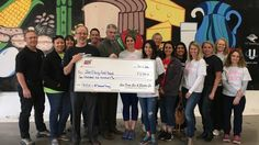 Employees volunteering through SDG&E's Season of Giving present San Diego Food Bank CEO, Jim Floros, with a $2,500 grant from the energy company.
