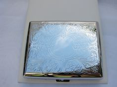 "This cigarette case is factory embossed with a fancy scroll work design covering the front and back. The front has a round framed area for engraving initials or a monogram. When closed the case measures a little over 4"" long x 3 3/8"" wide x 3/4"". The inside has springy bars to hold the cigarettes in place. This case holds a full pack of the longer 100s size cigarettes - ten on each side. Delivered to you in a gift box."