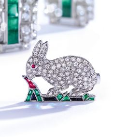 AN 18 KARAT WHITE GOLD AND GEM-SET BROOCH – Designed as a bunny set with round diamonds weighing approximately carats, amongst a garden set with calibré-cut emeralds and a ruby, completed by a ruby eye. From the Rachel 'Bunny' Mellon collection