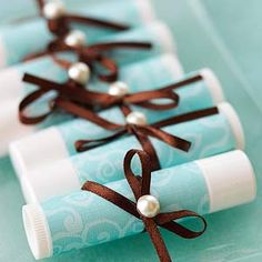 Lip Balm Favor  Design by Valerie Salmon  For this inexpensive and practical favor, remove the original packaging from a tube of lip balm, adhere a strip of paper around the barrel, and tie on a thin ribbon embellished with a pearl accent.  Editor's Tip: Use a very strong adhesive to secure the paper to the lip balm containers. Try a liquid quick-bond adhesive.