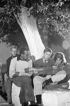 Leonard Cohen playing guitar in Hydra Greece where he bought a vacation home Marianne Ihlen is on his right October 1960