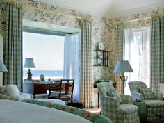 This quaint master bedroom brings the country and garden to the beach with floral wallpaper, checkered curtains and upholstered chairs all accented in sea foam green.