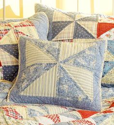 Beautifully quilted pillows in red, white, and blue fabrics that coordinate with the equally beautiful quilt.