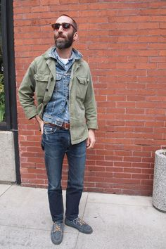 Denim jeans plus denim jacket with army green jacket thrown overtop. Brow leather belt, sunglasses, and boat shoes complete the look